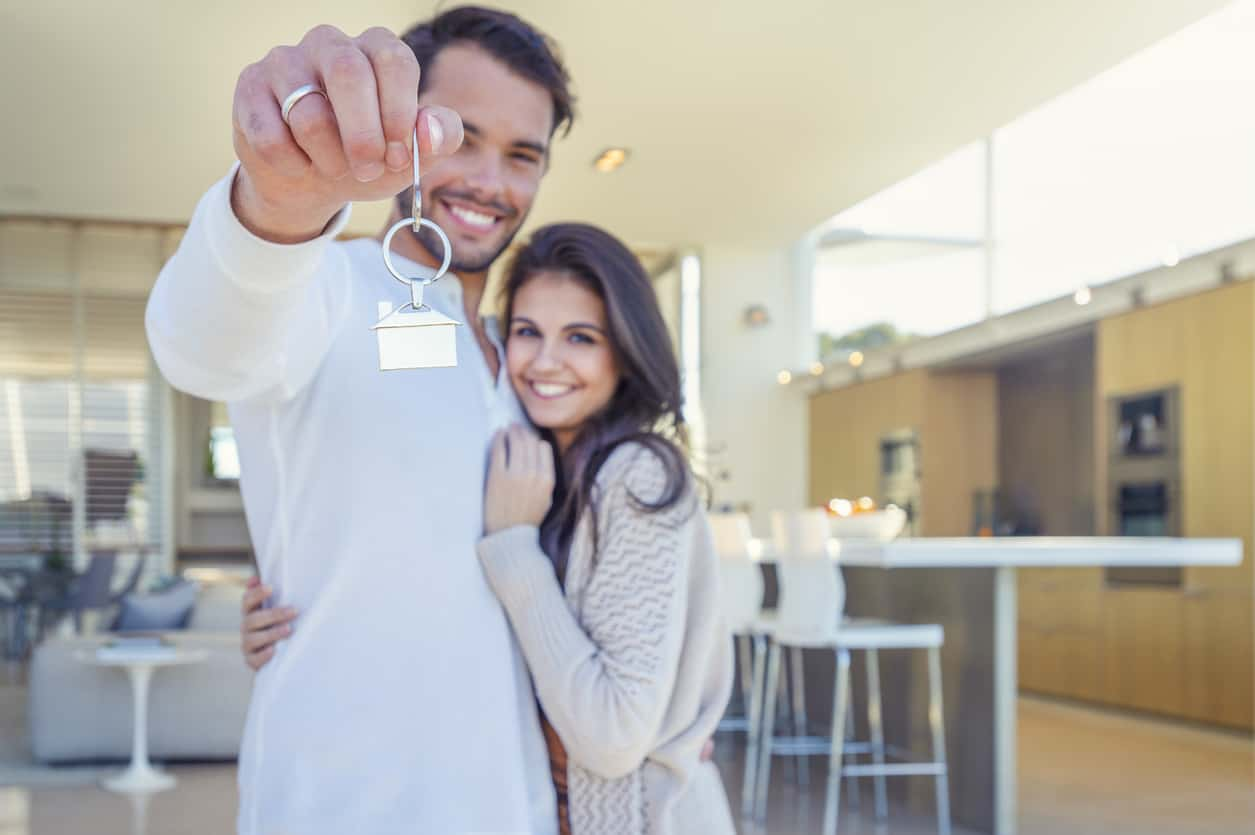 Happy couple holding a house key in their new home