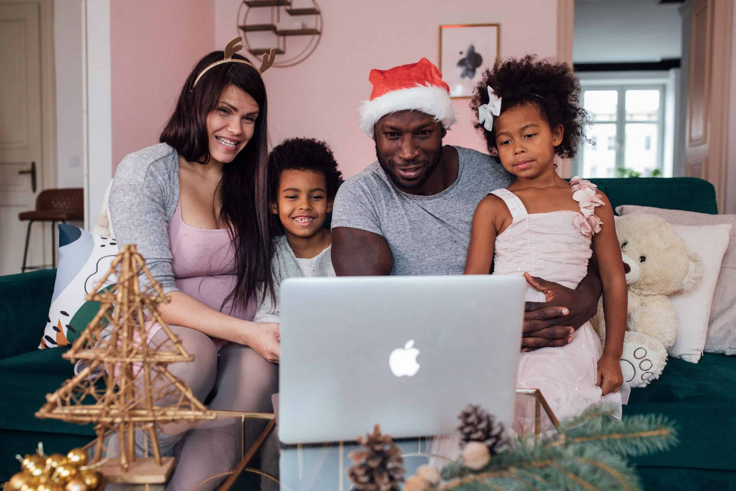 A family celebrating a socially distanced Christmas gathered in front of a laptop